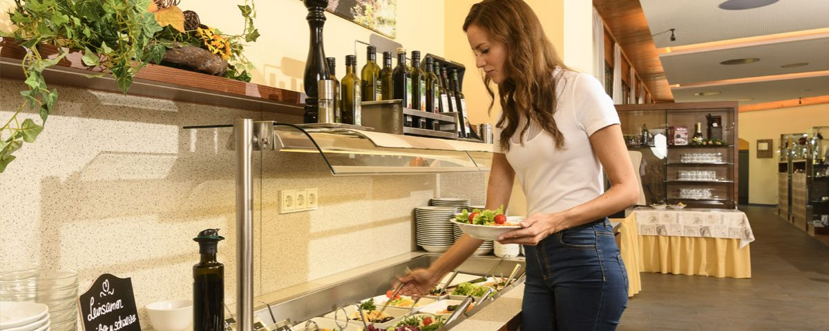 eine Dame am reichhaltigen Salatbuffet des Kur- und Gesundheitshotels Heilmoorbad Schwanberg