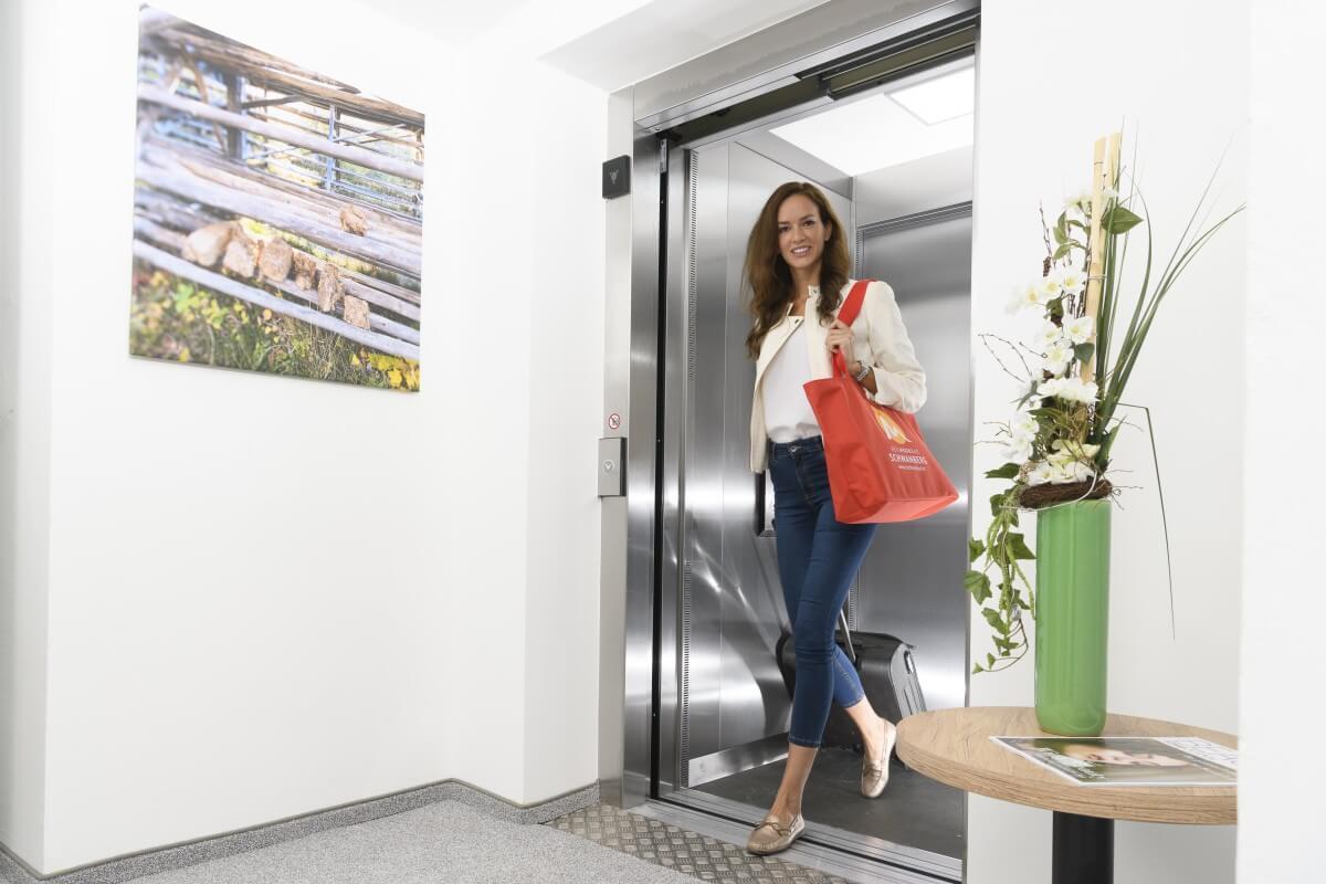 eine Dame verlässt den Lift im Kur- und Gesundheitshotel Heilmoorbad Schwanberg