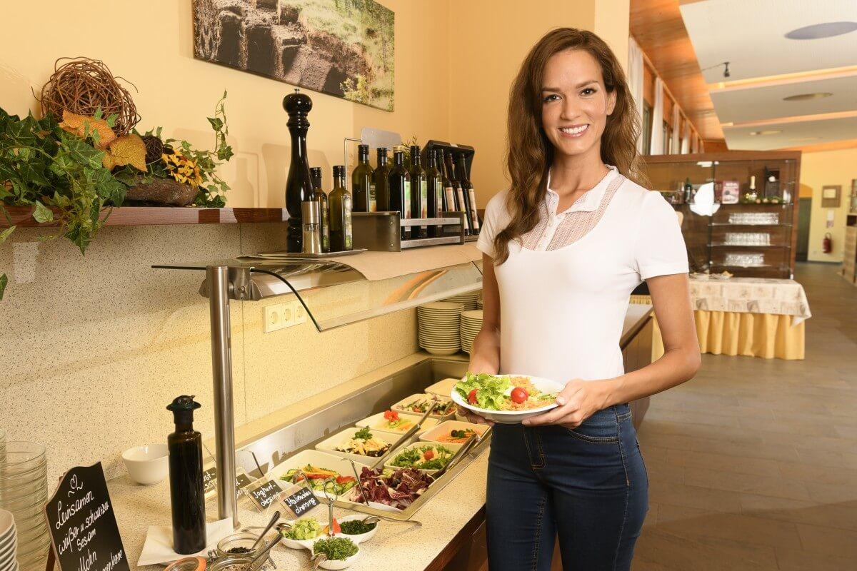 eine Dame vor dem reichhaltigen Salatbuffet des Kur- und Gesundheitshotels Heilmoorbad Schwanberg