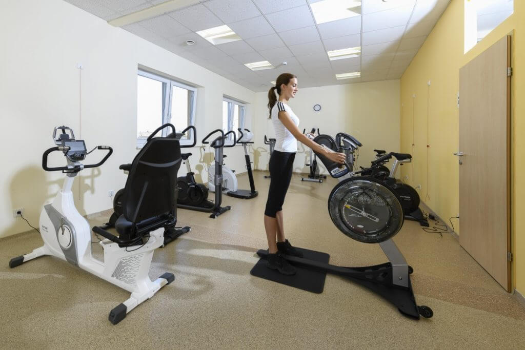 eine Dame im Fitnessraum an der Handkurbel im Kur- und Gesundheitshotel Heilmoorbad Schwanberg