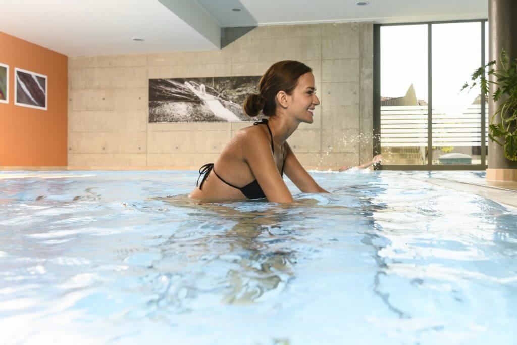 eine Dame im Hallenbad auf einem Aquabike im Kur- und Gesundheitshotel Heilmoorbad Schwanberg
