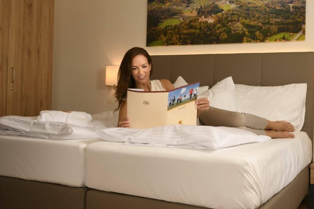 eine Dame relaxed auf einem Doppelbett im Kur- und Gesundheitshotel Heilmoorbad Schwanberg