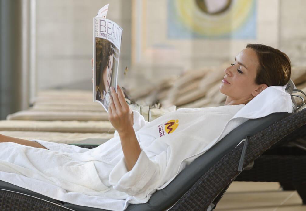 eine Dame relaxed am Liegestuhl mit einer Zeitschrift in der Hand