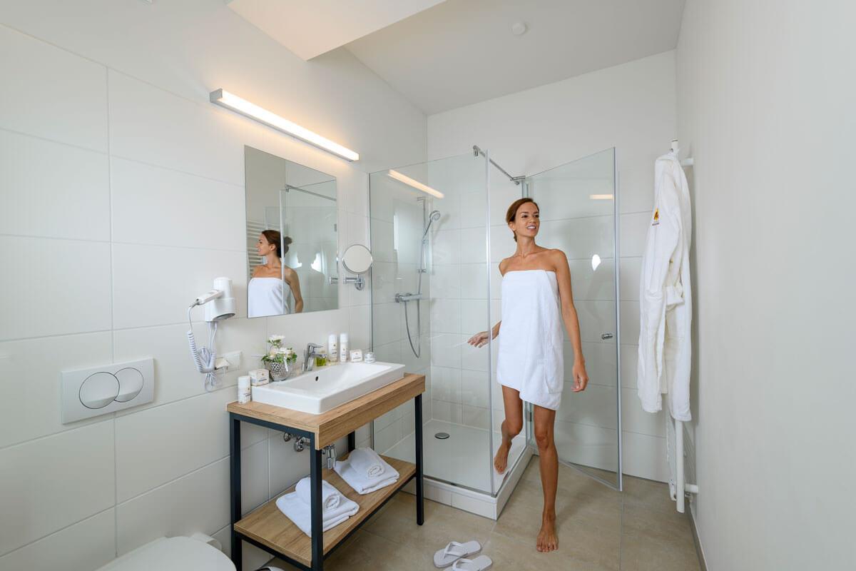 eine Dame steigt aus der Dusche eines geräumigen Badezimmers im Heilmoorbad Schwanberg