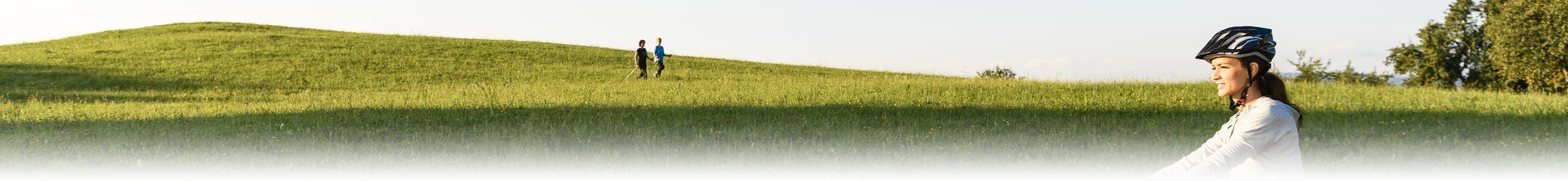 idylische Hügellandschaft mit walkenden und radfahrenden Personen