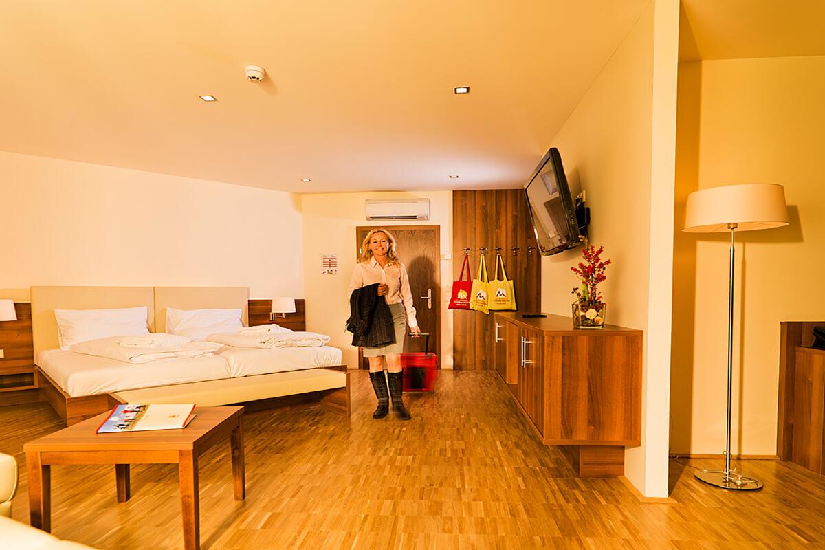 Dame mit Reisekoffer betritt eine Suite im Kur- und Gesundheitshotel Heilmoorbad Schwanberg