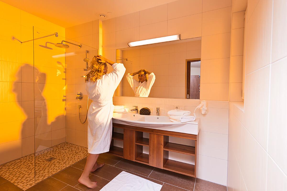 Dame im Badezimmer des Haupthauses im Kur- und Gesundheitshotel Heilmoorbad Schwanberg