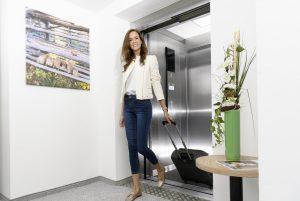Dame mit Reisekoffer beim Verlassen des Liftes im Kur- und Gesundheitshotel Heilmoorbad Schwanberg