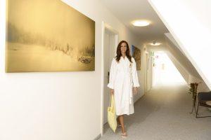 Dame im Bademantel auf Gang des Kur- und Gesundheitshotels Heilmoorbad Schwanberg